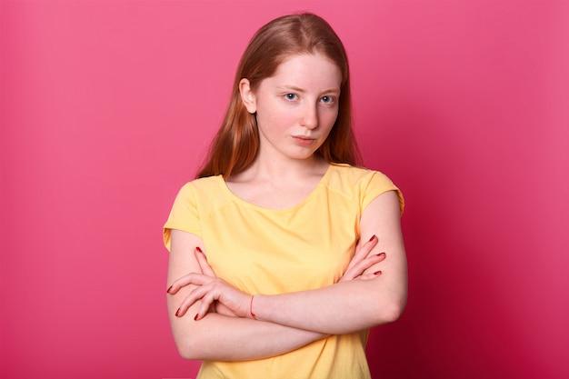 Ernstig hard meisje houdt armen over elkaar, gekleed geel casual t-shirt, geïsoleerd op roze. kopieer ruimte voor reclame of promotie.