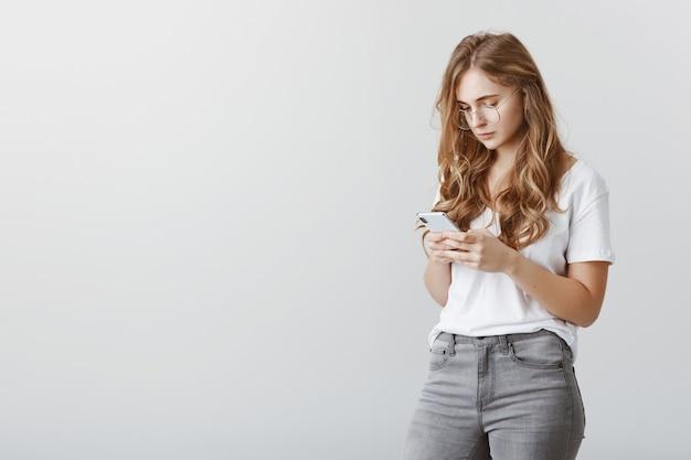 Ernstig jong blond meisje met behulp van mobiele telefoon, smartphonescherm kijken