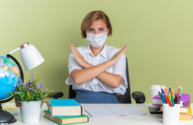 Ernstig jong blond studentenmeisje dat een beschermend masker draagt dat aan een bureau zit met schoolhulpmiddelen die naar de camera kijken en geen gebaar doen dat op een olijfgroene muur wordt geïsoleerd
