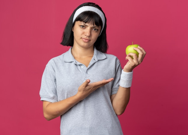 Ernstig jong fitnessmeisje met een hoofdband die een groene appel vasthoudt en naar een camera kijkt die het met een arm presenteert