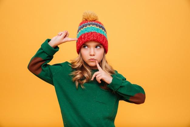 Ernstig jong meisje dat in sweater en hoed met vingers op tempel en dichtbijgelegen mond weg over sinaasappel kijkt