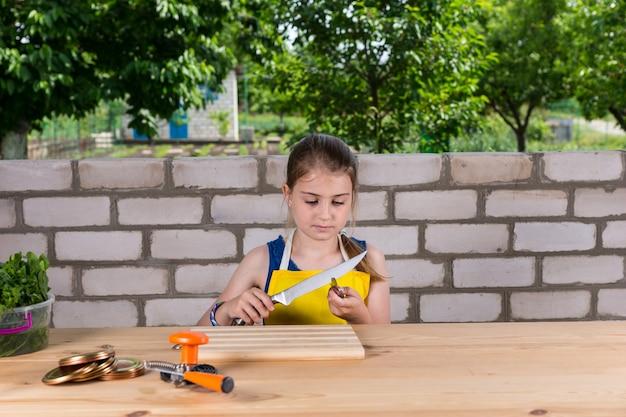Ernstig jong meisje met een schort, zittend aan een houten tafel met conservenbenodigdheden en het testen van de scherpte van het mes
