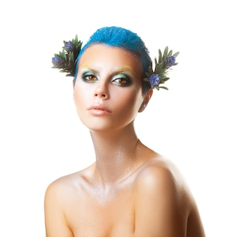 Ernstig jong meisje met kort blauw kapsel en veelkleurige make-up studio-opname geïsoleerd