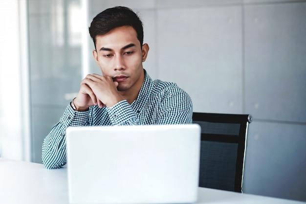 Ernstig jonge zakenman die aan computerlaptop werkt in bureau. hand op shin, zittend op een bureau met doordachte houding. geconcentreerde en slimme mannen