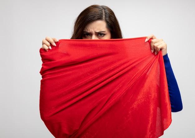 Ernstig kaukasisch superheldenmeisje houdt vast en kijkt naar de camera over rode cape