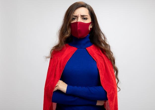 Ernstig kaukasisch superheromeisje met rode cape die rood beschermend masker draagt
