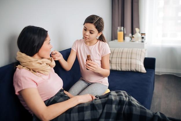 Ernstig kind zit op bank met zieke moeder. ze gaf haar wat siroop. jonge vrouw neemt het met mond. ze zitten samen in één kamer.
