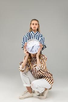 Ernstig langharig klein kind dat het gezicht van een volwassen vrouw bedekt met een gewone klok terwijl ze achter haar rug blijft