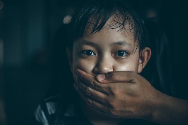 Ernstig meisje dat haar mond behandelt met de hand van een volwassene