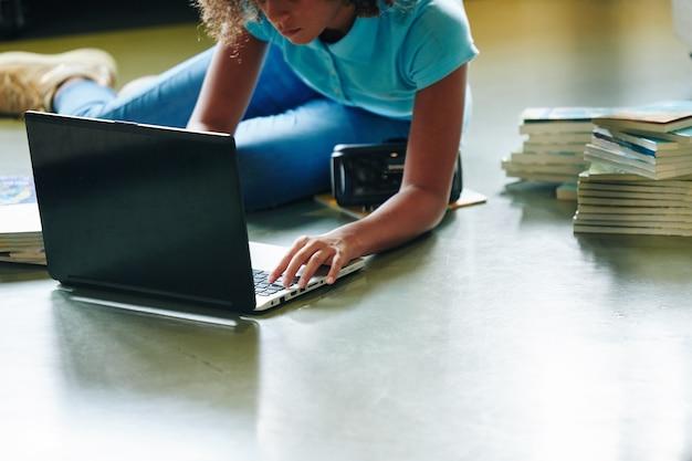 Ernstig meisje dat op de vloer met rond boeken ligt en aan laptop werkt Premium Foto