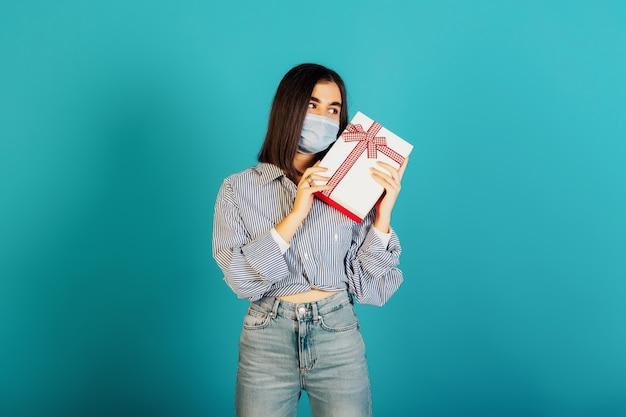 Ernstig meisje in een medisch masker met een witte geschenkdoos met rode strik geïsoleerd op blauwe achtergrond.