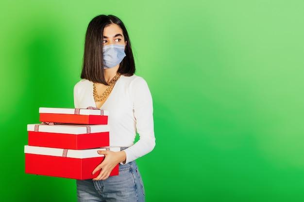 Ernstig meisje in medisch beschermend masker met kerstmisgiften in een staande dozen