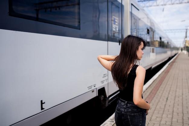 Ernstig meisje met haar rug op de zijkant van een trein