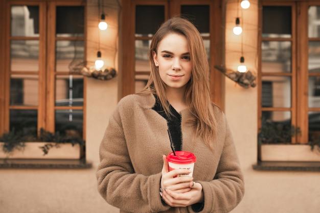 Ernstig meisje staat in de straat op de achtergrond van architectuur, draagt een beige jas, houdt een kopje koffie in haar handen, kijkt in de camera en lacht
