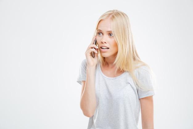 Ernstig mooi blond meisje dat een telefoongesprek voert geïsoleerd op een witte muur