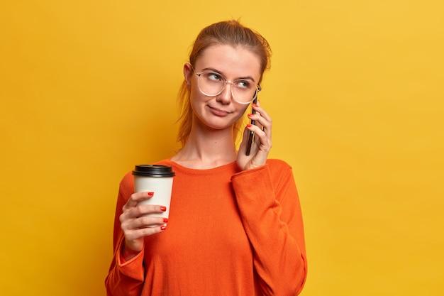 Ernstig mooi europees meisje heeft een saai telefoongesprek, hangt een keer rond, praat met een persoon, houdt wegwerpkoffie vast, maakt gebruik van moderne technologieën, gekleed in trui, poseert over gele muur