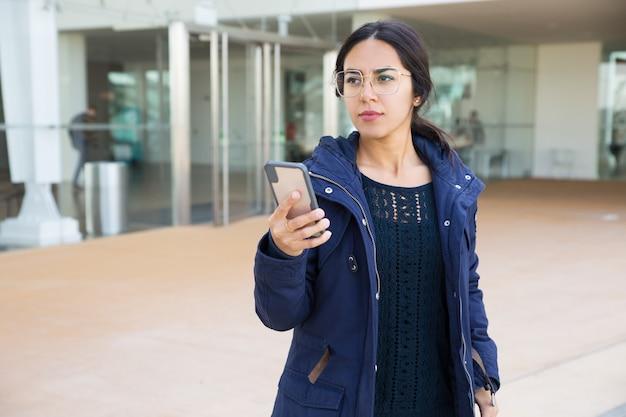 Ernstig mooi meisje dat mobiele app gebruikt
