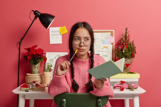 Ernstig nadenkend aziatisch meisje met gekamde vlechten, houdt notitieboekje en potlood vast, schrijft toekomstige plannen en doelen voor de komende kerst