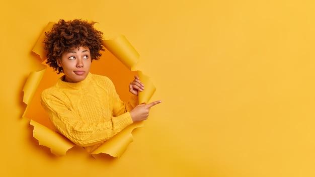 Ernstig nadenkend duizendjarig meisje met donkere huid en afro-borstelig haar wijst weg op kopie ruimte