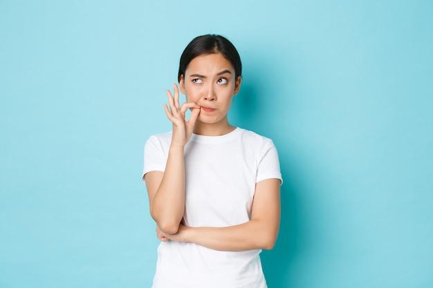 Ernstig ogende jonge aziatische vrouw vastberaden belofte nakomen en zwijgen, geheim verbergen, nadenkende linkerbovenhoek kijken en lippen vergrendelen, zegel- of ritssluitinggebaar maken over mond, blauwe muur