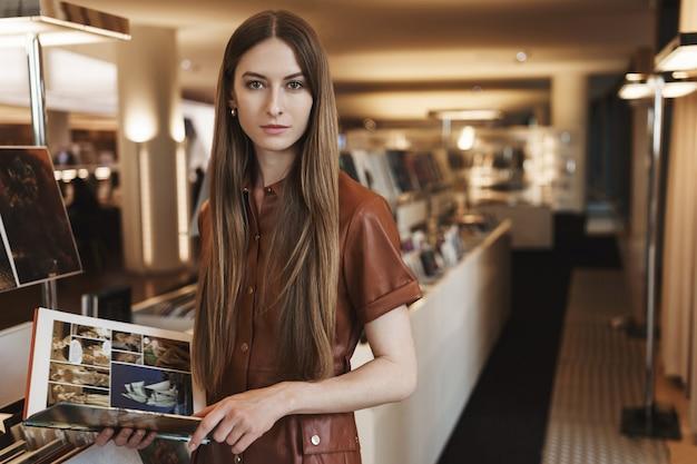 Ernstig ogende jonge vrouw designtijdschriften plukken in vintage winkel, staande in stijlvolle bruine jurk.