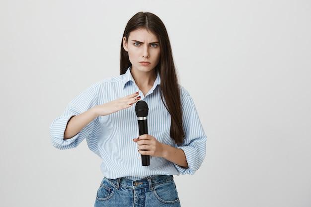 Ernstig ogende vrouw die microfoon controleert