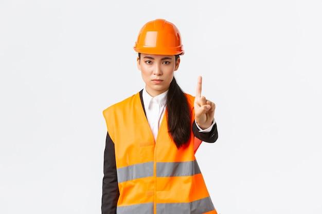Ernstig ogende zelfverzekerde en ontevreden aziatische vrouwelijke ingenieur