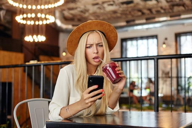 Ernstig op zoek verrast jonge langharige blonde vrouw onverwacht nieuws lezen met een ontevreden gezicht, bessen drankje met rietje drinken zittend aan tafel boven modern café