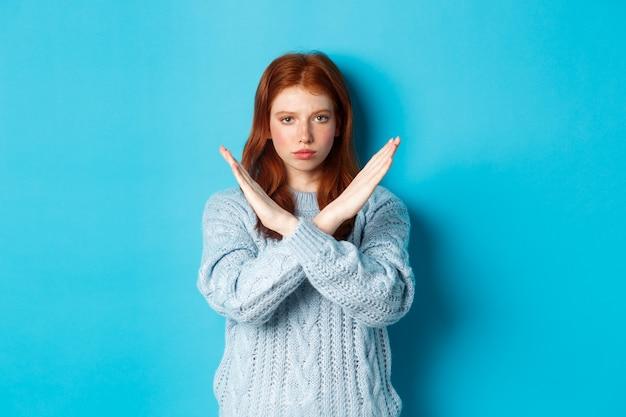 Ernstig roodharig meisje dat er zelfverzekerd uitziet, een kruisgebaar toont om te stoppen en actie te verbieden, staande over een blauwe achtergrond.