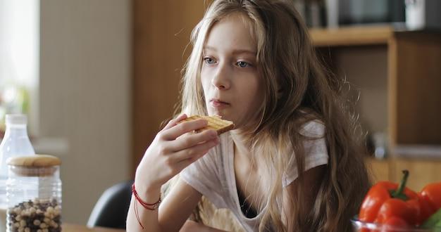 Ernstig schoolmeisje met lang haar eet witbrood een kind eet toast in de keuken