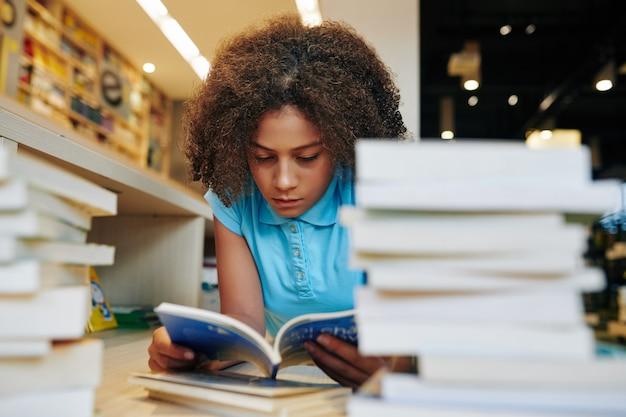 Ernstig tienermeisje lezen studentenboek in bibliotheek voor groot schoolproject