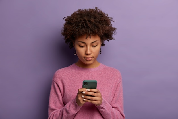 Ernstig uitziende afro-amerikaanse vrouw bericht leest op moderne mobiele telefoon, surft op sociale media, heeft geconcentreerde blik in display, draagt casual trui