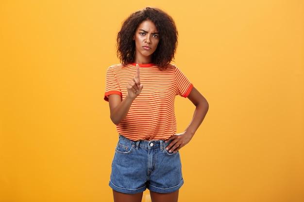 Ernstig uitziende afro-amerikaanse vrouw fronst en schudt wijsvinger in verbieden of stop gebaar over oranje muur