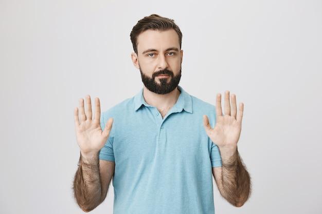 Ernstig uitziende bebaarde man met stopgebaar, lege handen