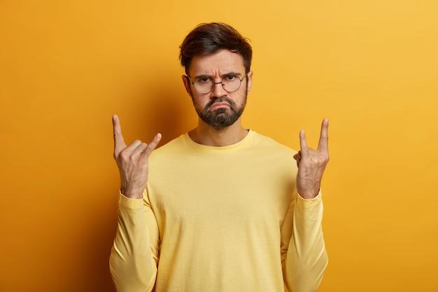 Ernstig uitziende bebaarde man toont cool rock-'n-roll-gebaar, maakt heavy metal-bord, is een echte rocker, draagt een optische bril en springt tegen de gele muur op het concert van de favoriete band