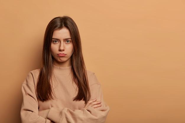 Ernstig uitziende beledigde europese vrouw portretteert de lippen, houdt de handen gekruist, heeft een sombere, boos uitdrukking, klaagt, draagt een bruine sweater