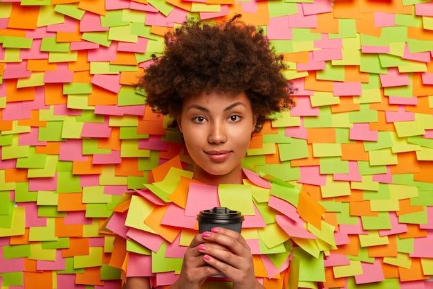 Ernstig uitziende etnische kantoormedewerker heeft koffiepauze, houdt afhaaldrankje in handen, kijkt direct naar de camera, praat met collega, vormt binnen tegen zelfklevende notities op de muur. mensen, drinken