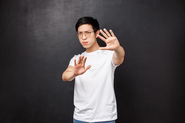 Ernstig uitziende geïrriteerde en ontstemde aziatische man die zegt dat hij ermee moet ophouden, bedek het gezicht met handen alsof hij zichzelf verdedigt tegen glimmend licht, zijn ogen dichtknijpt met een te felle lamp,