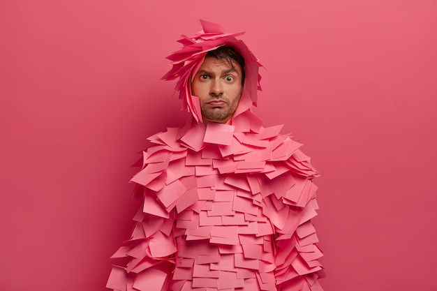 Ernstig uitziende jonge europese man trekt wenkbrauwen op, luistert aandachtig naar informatie, bereidt zich voor op kantoorkostuumfeest, bedekt met zelfklevende notities, poseert tegen roze muur. monochroom