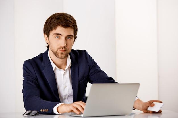 Ernstig uitziende knappe zakenman in pak, zit bureau, werkt aan rapport met laptop, wacht op telefoontje