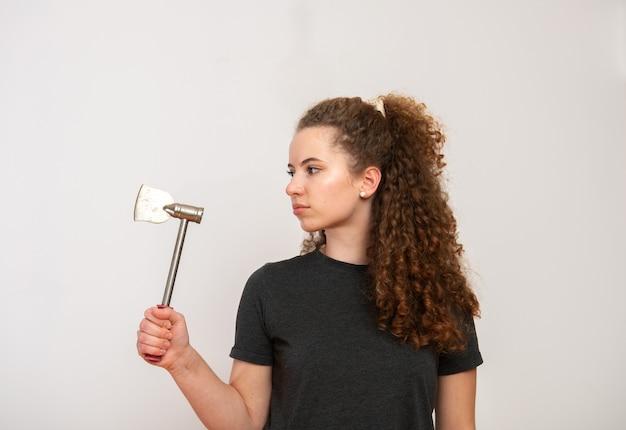 Ernstig uitziende tiener met bruin krullend haar in de hand houden bijl op een witte achtergrond