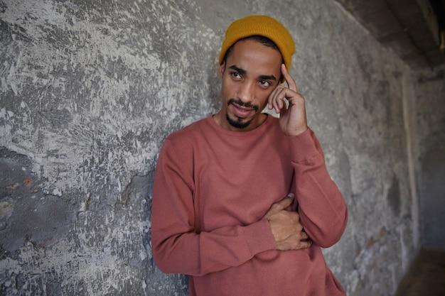 Ernstig uitziende, vrij donkere man met baard, roze trui en mosterd hoofdtooi, leunend op betonnen muur tijdens een ernstig gesprek