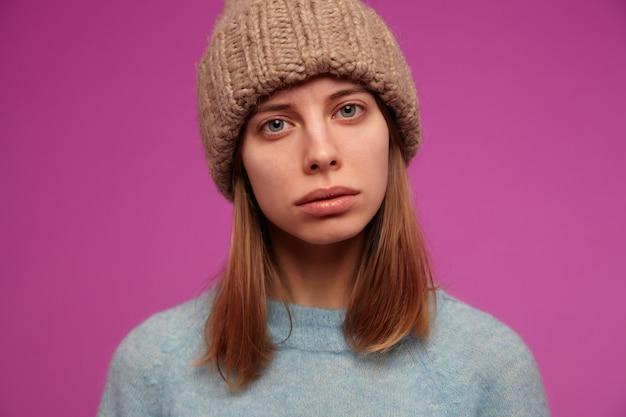 Ernstig uitziende vrouw, mooi meisje met donkerbruin haar. het dragen van blauwe trui en gebreide muts. in afwachting van je antwoord.