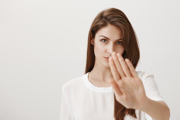 Ernstig uitziende vrouw steekt haar hand uit om stopgebaar te tonen, keurt actie af