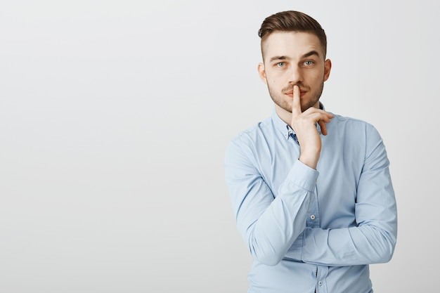 Ernstig uitziende zakenman zegt shh, maakt een zwijg gebaar, heeft stilte nodig om na te denken