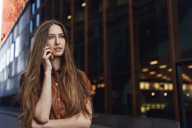 Ernstig uitziende zelfverzekerde prachtige vrouw die op de mobiele telefoon spreekt.