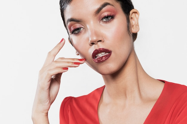 Ernstig vrouwelijk model dat levendige kleding en make-up draagt