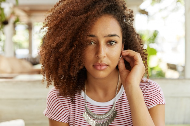 Ernstig vrouwelijk model met een donkere huidskleur en een aantrekkelijke uitstraling, kijkt met haar lichtbruine ogen, denkt ergens na, geniet van recreatietijd in café. mensen, levensstijl, gezichtsuitdrukkingen concept