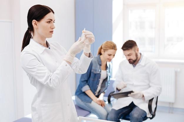 Ernstige aangename professionele arts die een spuit vasthoudt en ernaar kijkt terwijl hij klaar is om een injectie te doen