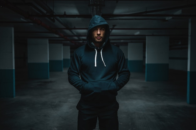 Ernstige aantrekkelijke gespierde kaukasische sportman in hoodie staande in ondergrondse garage met handen in de zakken 's nachts. stedelijk leven concept.